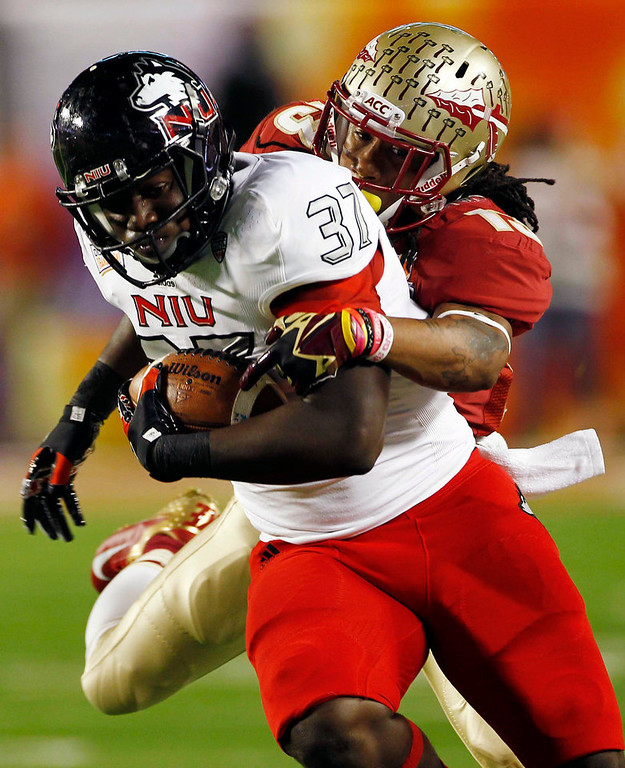 Description of . Northern Illinois tight end Desroy Maxwell (37) is tackled by Florida State defensive back Ronald Darby (13) during the first half of the Orange Bowl NCAA college football game, Tuesday, Jan. 1, 2013, in Miami. (AP Photo/J Pat Carter)
