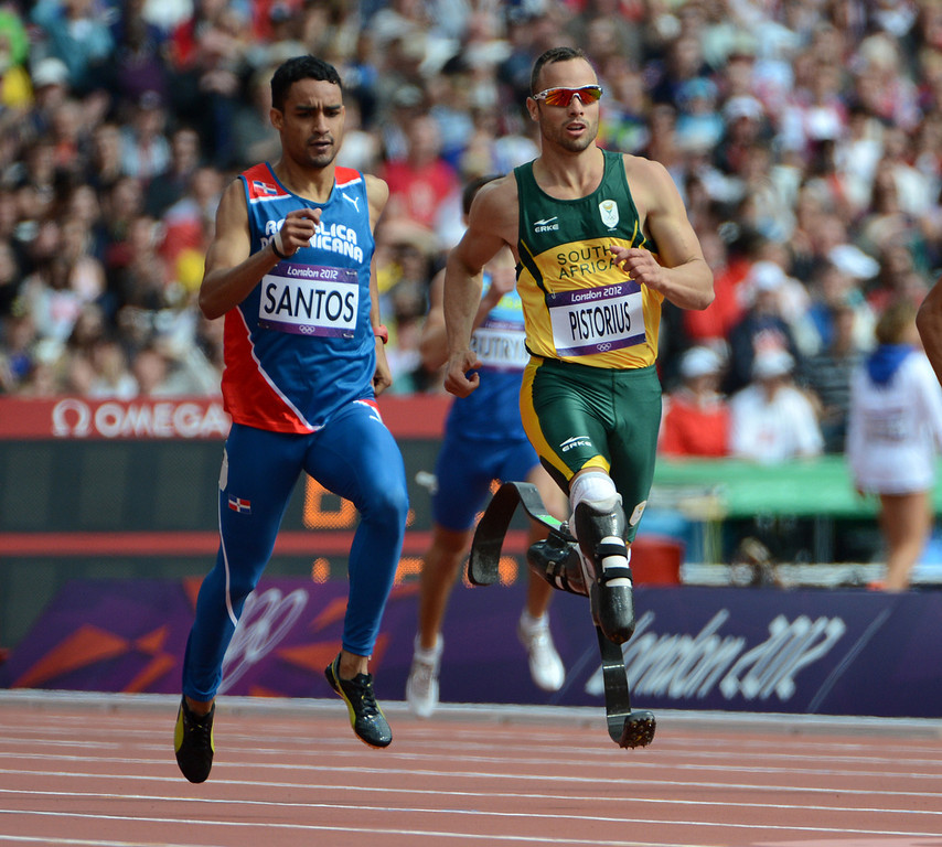 Description of . South Africa's Oscar Pistorius, center, runs next to Dominican Republic's Luguelin Santos in their Men's 400m heat at the Olympic Stadium for the London 2012 Olympics in London, England on Saturday, Aug. 4, 2012.  (Nhat V. Meyer/Mercury News)