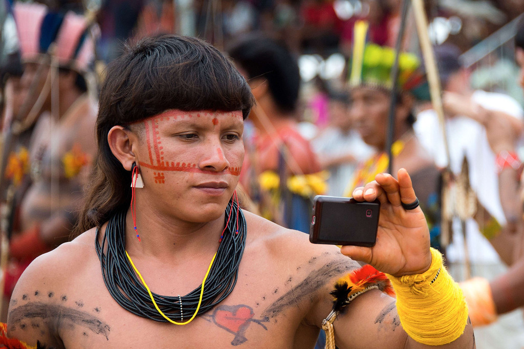 Description of . An indigenous man records participants of the bow and arrow competition with his mobile phone during the XII International Games of Indigenous Peoples in Cuiaba, Mato Grosso state, Brazil on November 12, 2013. 1AFP PHOTO / Christophe SIMON/AFP/Getty Images
