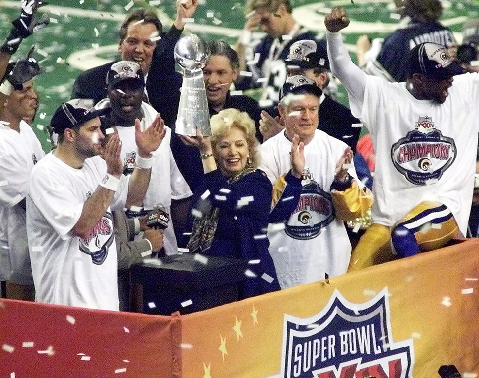 Description of . St. Louis Rams owner Georgia Frontiere holds the Lombardi Trophy as quarterback Kurt Warner (L) and head coach Dick Vermeil (2nd R) look on during Super Bowl XXXIV at the Georgia Dome in Atlanta, GA 30 January, 2000. The Rams defeated the Tennessee Titans 23-16 to win the NFL championship. PETER NEWCOMB/AFP/Getty Images