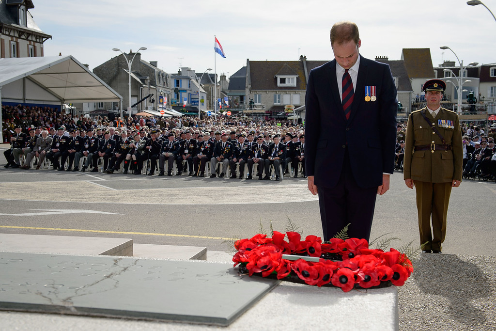 Description of . Britain's Prince William, Duke of Cambridge, lays a wreath at an event for veterans in Arromanches-les-Bains, western France, Friday, June 6, 2014, marking the 70th anniversary of the World War II Allied landings in Normandy.  (AP Photo/Leon Neal, Pool)