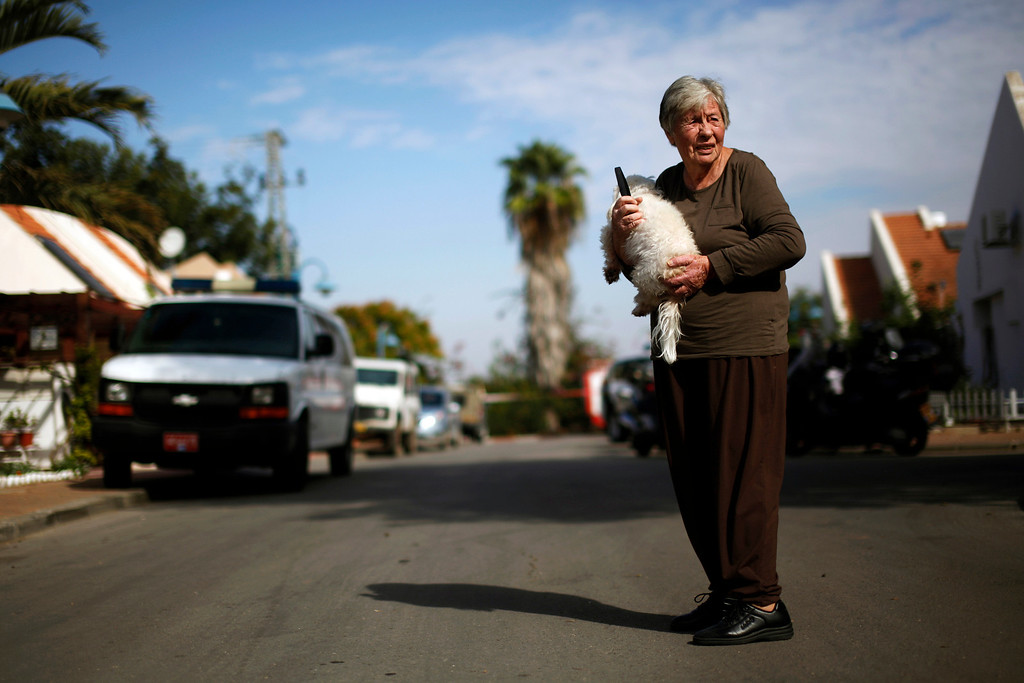 Description of . An Israeli woman holds a dog as she stands near the scene where a rocket landed in Arugot, east of Ashdod November 21, 2012. REUTERS/Amir Cohen