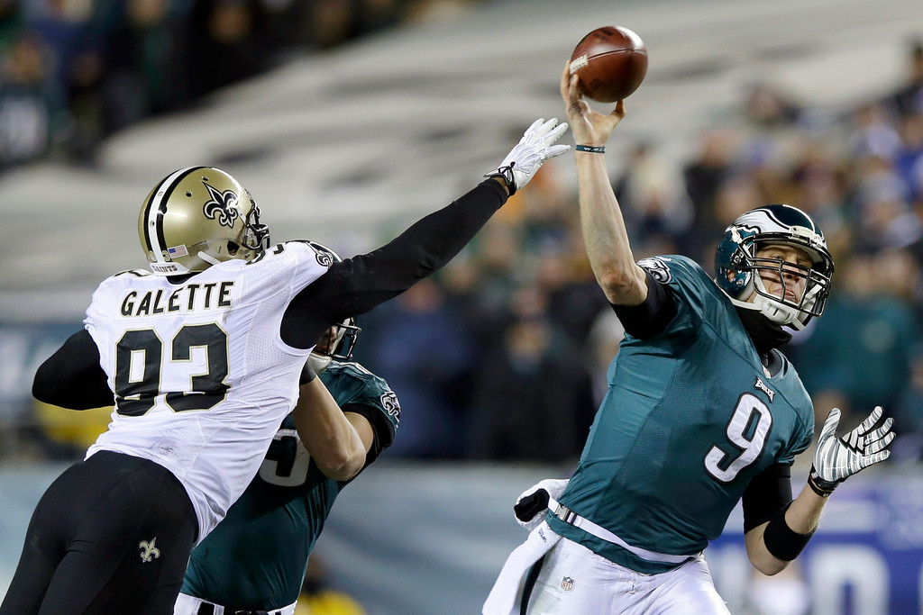 Description of . Philadelphia Eagles' Nick Foles (9) passes as New Orleans Saints' Junior Galette (93) tries to block during the first half of an NFL wild-card playoff football game, Saturday, Jan. 4, 2014, in Philadelphia. (AP Photo/Michael Perez)