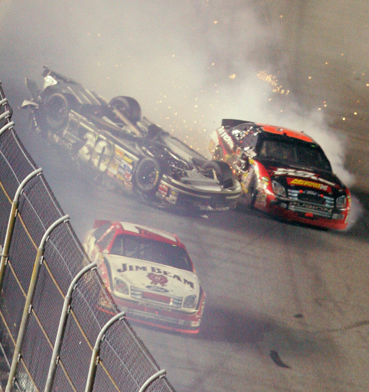 Description of . Clint Bowyer slides upside down following a crash on the final lap of the NASCAR Daytona 500 auto race at Daytona International Speedway in Daytona Beach, Fla., Sunday, Feb. 18, 2007. Robby Gordon is at front. (AP Photo/David Graham)