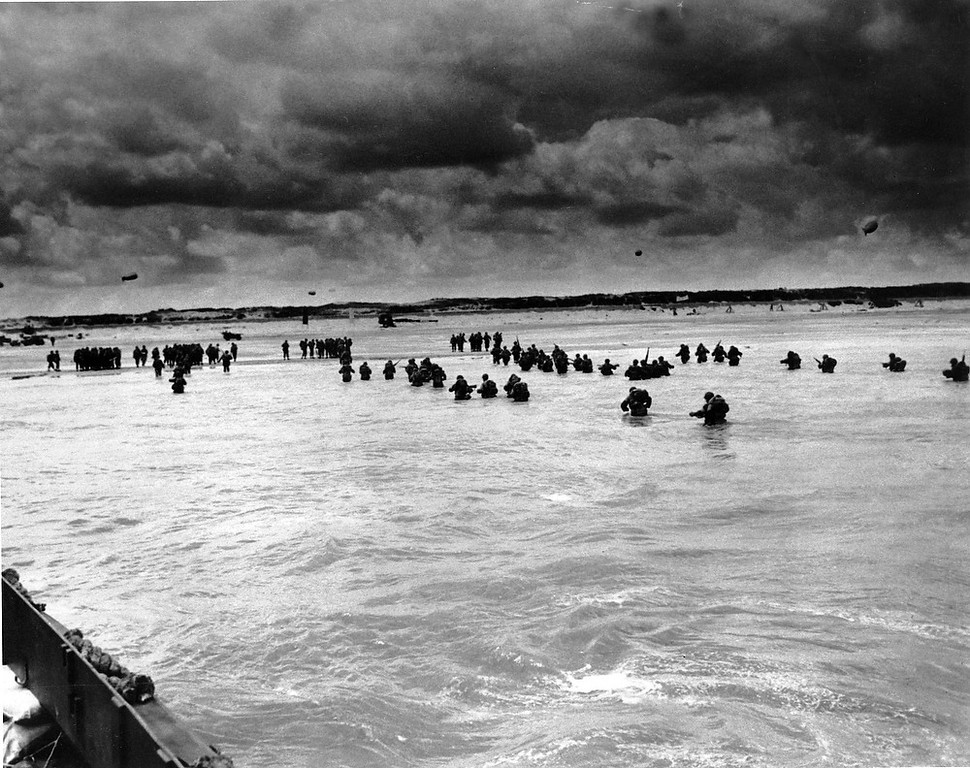 Description of . U.S. reinforcements wade through the surf as they land at Normandy in the days following the Allies' June 1944, D-Day invasion of occupied France.  (AP Photo/Peter Carroll)