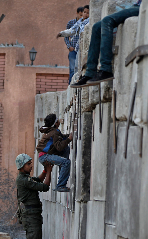 Description of . An Egyptian army soldier helps a boy climb cement blocks in front of the presidential palace in Cairo, Egypt, Sunday, Dec. 9, 2012. Egypt\'s liberal opposition called for more protests Sunday, seeking to keep up the momentum of its street campaign after the president made a partial concession overnight but refused its main demand he rescind a draft constitution going to a referendum on Dec. 15. (AP Photo/Petr David Josek)