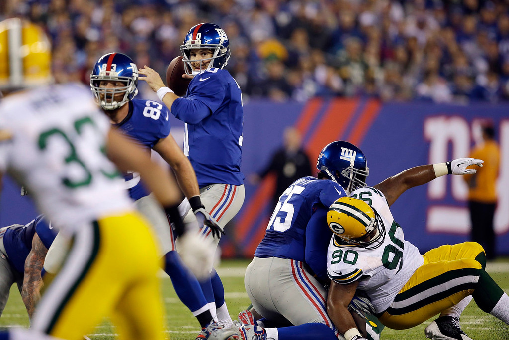 Description of . New York Giants quarterback Eli Manning, center, throws a pass to Rueben Randle for a touchdown during the first half of an NFL football game against the Green Bay Packers, Sunday, Nov. 17, 2013, in East Rutherford, N.J. (AP Photo/Seth Wenig)