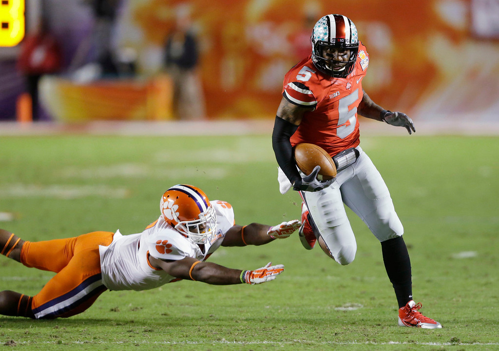 Description of . Ohio State quarterback Braxton Miller (5) runs past Clemson safety Robert Smith on his way to a touchdown during the first half of the Orange Bowl NCAA college football game, Friday, Jan. 3, 2014, in Miami Gardens, Fla. (AP Photo/Wilfredo Lee)
