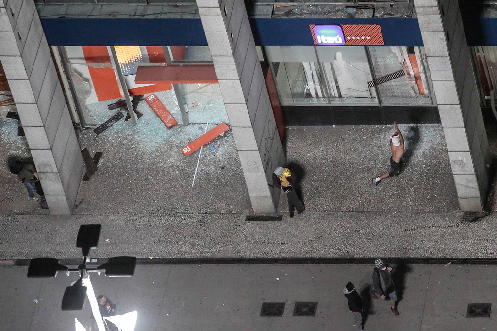 Description of . People vandalize a Bank Itau branch during a students protest in Sao Paulo, Brazil on June 18, 2013, against a recent rise in public bus and subway fare from 3 to 3.20 reais (1.50 USD).  President Dilma Rousseff vowed Tuesday to listen to youths staging Brazil's biggest protests in 20 years in an outpouring of anger over the huge cost of staging events like the World Cup.    Miguel Schincariol/AFP/Getty Images