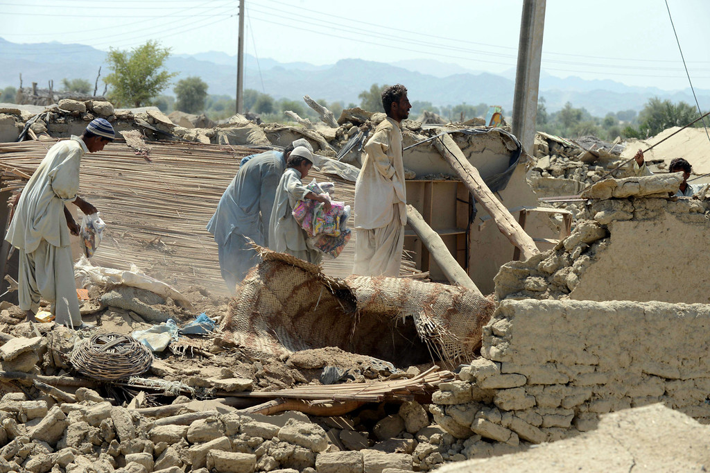 Description of . Pakistani earthquake survivors collect their belongings in rubble of their collapsed mud houses in the earthquake-devastated district of Awaran on September 25, 2013.     AFP PHOTO/Banaras KHAN/AFP/Getty Images
