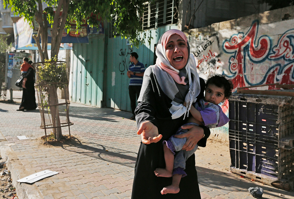 Description of . A woman cries as Palestinians flee their homes in the Shajaiyeh neighborhood of Gaza City, after Israel had airdropped leaflets warning people to leave the area, Wednesday, July 16, 2014. A Hamas website says Israel has fired missiles at the homes of four of its senior leaders as it resumed bombardment of Gaza, following a failed Egyptian cease-fire effort. Health officials say the Palestinian death toll in nine days of fighting has reached 204. (AP Photo/Lefteris Pitarakis)