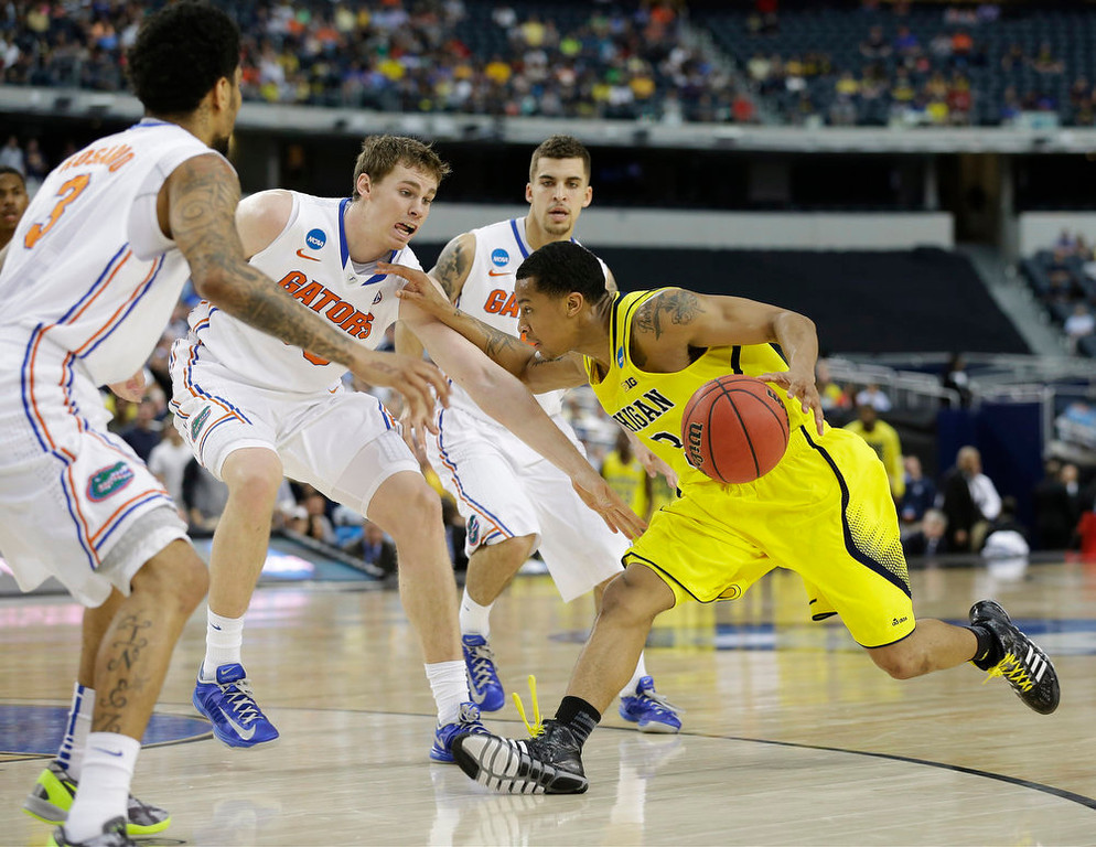 Description of . Michigan\'s Trey Burke (3) drives against Florida\'s Mike Rosario (3), Erik Murphy, second from left, and Scottie Wilbekin during the first half of a regional final game in the NCAA college basketball tournament, Sunday, March 31, 2013, in Arlington, Texas. (AP Photo/Tony Gutierrez)