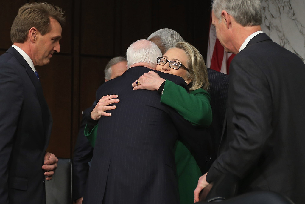 Description of . WASHINGTON, DC - JANUARY 23:  U.S. Secretary of State Hillary Clinton embraces Sen. John McCain (R-AZ) as  Senate Foreign Relations Committee members Sen. Jeff Flake (R-AZ) (L) and Sen. Ron Johnson (R-WI) look on before a hearing with the Senate Foreign Relations Committee on Capitol Hill January 23, 2013 in Washington, DC. Lawmakers questioned Clinton about the security failures during the September 11 attacks against the U.S. mission in Benghazi, Libya, that led to the death of four Americans, including U.S. Ambassador Christopher Stevens. (Photo by Chip Somodevilla/Getty Images)