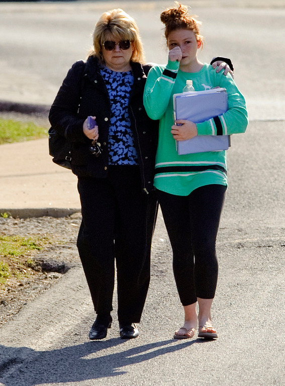 Description of . A student and guardian walk to their car from Franklin Regional Middle School after more then a dozen students were stabbed by a knife wielding suspect at nearby Franklin Regional High School on Wednesday, April 9, 2014, in Murrysville, Pa., near Pittsburgh. The suspect, a male student, was taken into custody and is being questioned. (AP Photo/Tribune Review, Brian F. Henry)