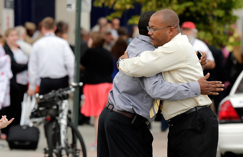 Description of . Two men embrace at a gathering point for family members of Navy Yard employees that was set up inside Nationals Park in the wake of the shooting September 16, 2013 in Washington, DC. Police believe at least one gunman shot and killed at least 12 people and wounded others in an incident that put parts of the city on lockdown. (Photo by Win McNamee/Getty Images)