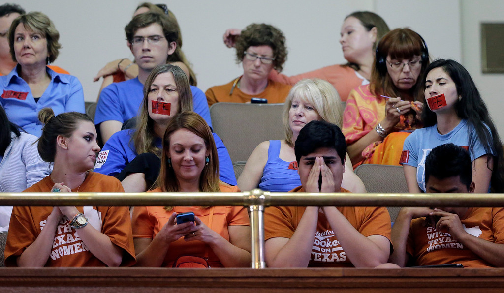Description of . Supporters and opponents of an abortion bill, mostly dressed in blue or orange to show their side, sit in the gallery of the Texas Senate chambers as lawmakers debate before the final vote, Friday, July 12, 2013, in Austin, Texas. The bill would require doctors to have admitting privileges at nearby hospitals, only allow abortions in surgical centers, dictate when abortion pills are taken and ban abortions after 20 weeks. (AP Photo/Eric Gay)