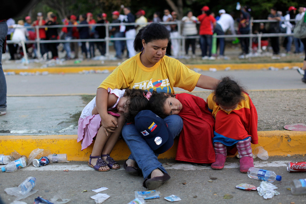 Description of . A woman sits with three girls outside the military academy where a funeral ceremony will take place for Venezuela's late President Hugo Chavez in Caracas, Venezuela, Friday, March 8, 2013.  (AP Photo/Rodrigo Abd)