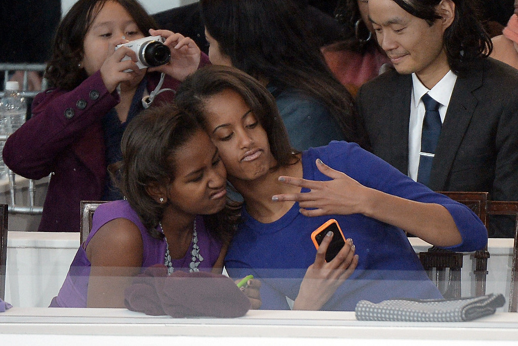 Description of . Sasha (L) and Malia Obama, daughters of U.S. President Barack Obama, take a photo of themselves during the Presidential Inaugural Parade on January 21, 2013 in Washington, DC.   JOE KLAMAR/AFP/Getty Images