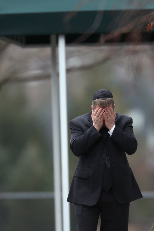 Description of . A man covers his face with his hands as people arrive for the funeral services of six year-old Noah Pozner, who was  killed in the shooting massacre in Newtown, CT, at Abraham L. Green and Son Funeral Home on December 17, 2012 in Fairfield, Connecticut. Today is the first day of funerals for some of the twenty children and seven adults who were killed by 20-year-old Adam Lanza on December 14, 2012.  (Photo by Spencer Platt/Getty Images)