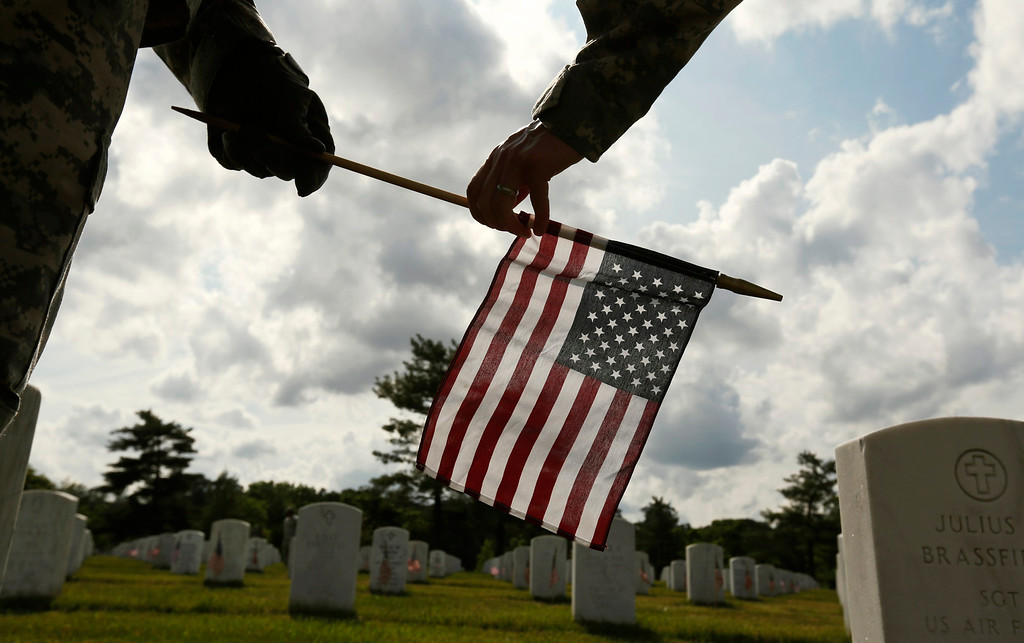 Description of . Soldiers from the Third U.S. Infantry Regiment (The Old Guard) place a flag at a grave at Arlington National Cemetery in Virginia May 23, 2013. The annual