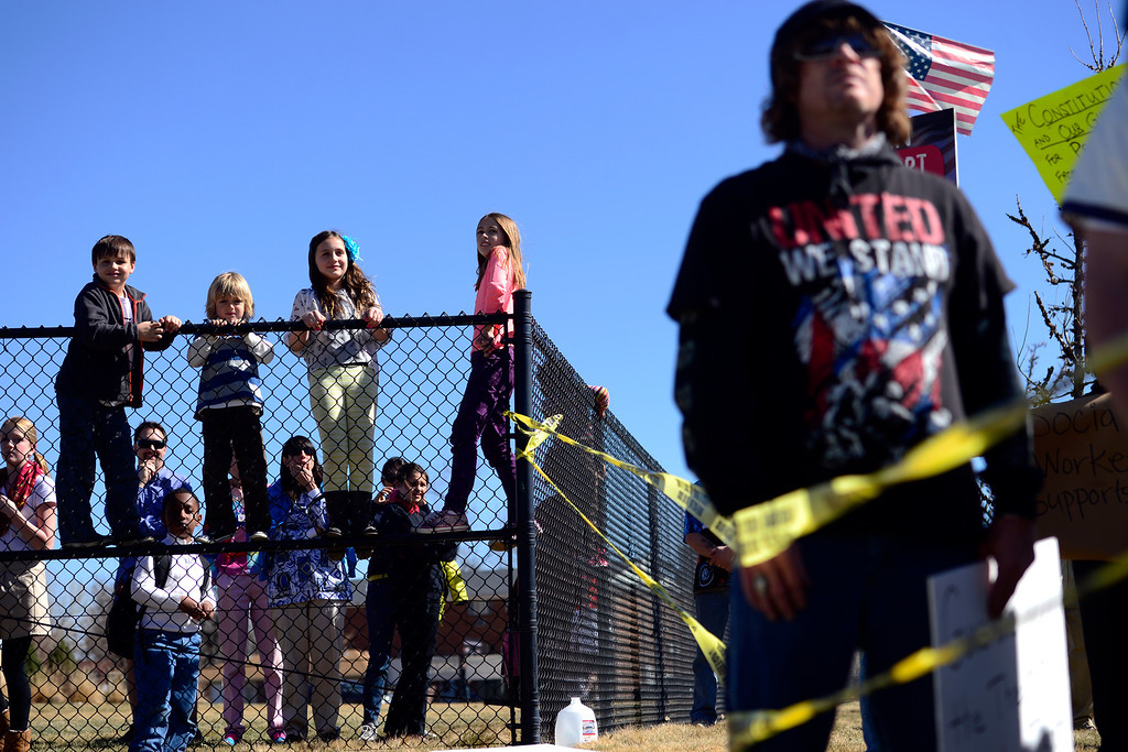 Description of . DENVER, CO - APRIL 3: From left to right, Wade Jahnke, 7, Sam Pozzetta, 6, Avarie Jahnke, 9, and Sophia Pozzetta, 10, stand on the fence of Bill Roberts School to get a better view as Barack Obama's motorcade leaves after a speech at the Denver Police Academy. Both sides gathered outside of the complex to share their respective views. (Photo by AAron Ontiveroz/The Denver Post)