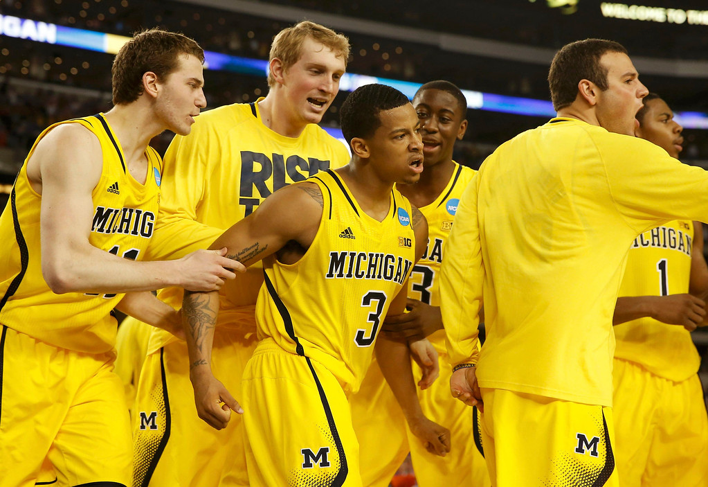 Description of . Michigan Wolverines guard Trey Burke (3) celebrates with teammates after shooting a three point basket to tie the game against the Kansas Jayhawks during the second half in their South Regional NCAA men\'s basketball game in Arlington, Texas March 29, 2013. REUTERS/Jim Young