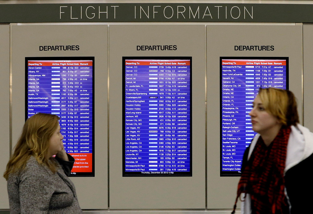 Description of . A flight information screen displays canceled flights as passenger walk at Midway airport in Chicago, Thursday, Dec. 20, 2012. The first widespread snowstorm of the season crawled across the Midwest on Thursday, with whiteout conditions stranding holiday travelers. The storm led airlines to cancel about 1,000 flights ahead of the Christmas holiday ó relatively few compared to past big storms, though the number was climbing.  Southwest Airlines scratched all of its flights scheduled after 4:30 p.m. today at Midway. (AP Photo/Nam Y. Huh)
