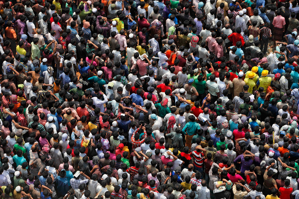 Description of . Bangladeshis crowd to watch rescue work in progress at the site of a building that collapsed Wednesday in Savar, near Dhaka, Bangladesh, Thursday, April 25, 2013. (AP Photo/A.M. Ahad)