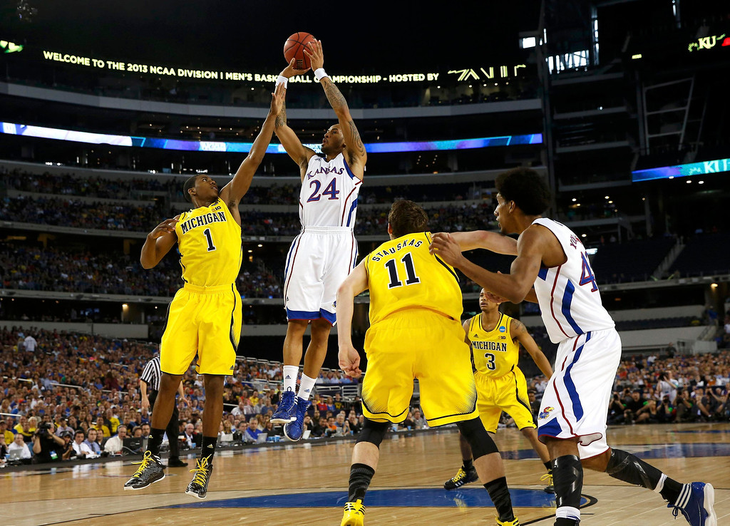 Description of . Kansas Jayhawks guard Travis Releford (24) shoots over Michigan Wolverines forward Glenn Robinson III during the first half in their South Regional NCAA mens basketball game in Arlington, Texas March 29, 2013. REUTERS/Jim Young