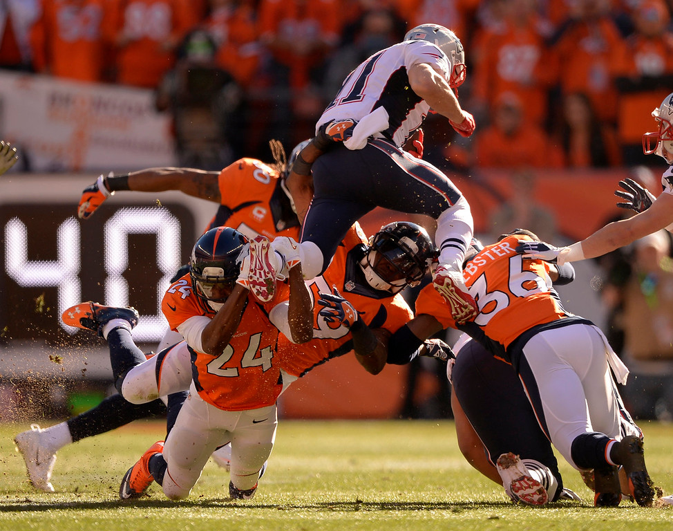 Description of . New England Patriots wide receiver Julian Edelman (11) tries to leap over the Broncos but Denver Broncos cornerback Champ Bailey (24) has him by the foot during the first quarter. The Denver Broncos vs. The New England Patriots in an AFC Championship game  at Sports Authority Field at Mile High in Denver on January 19, 2014. (Photo by John Leyba/The Denver Post)