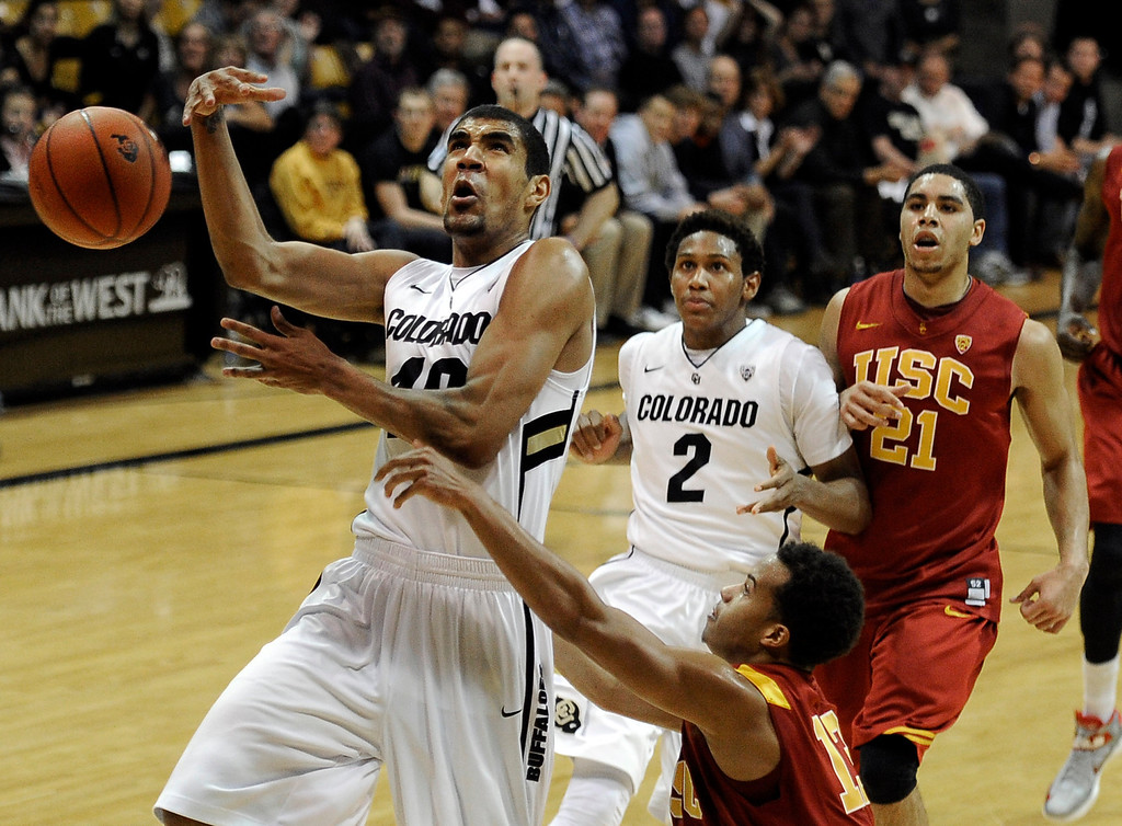 Description of . University of Colorado's Josh Scott gets fouled by Chass Bryan while going for a layup during a game against the University of Southern California on Thursday, Jan. 10, at the Coors Event Center on the CU campus in Boulder. Jeremy Papasso/Daily Camera
