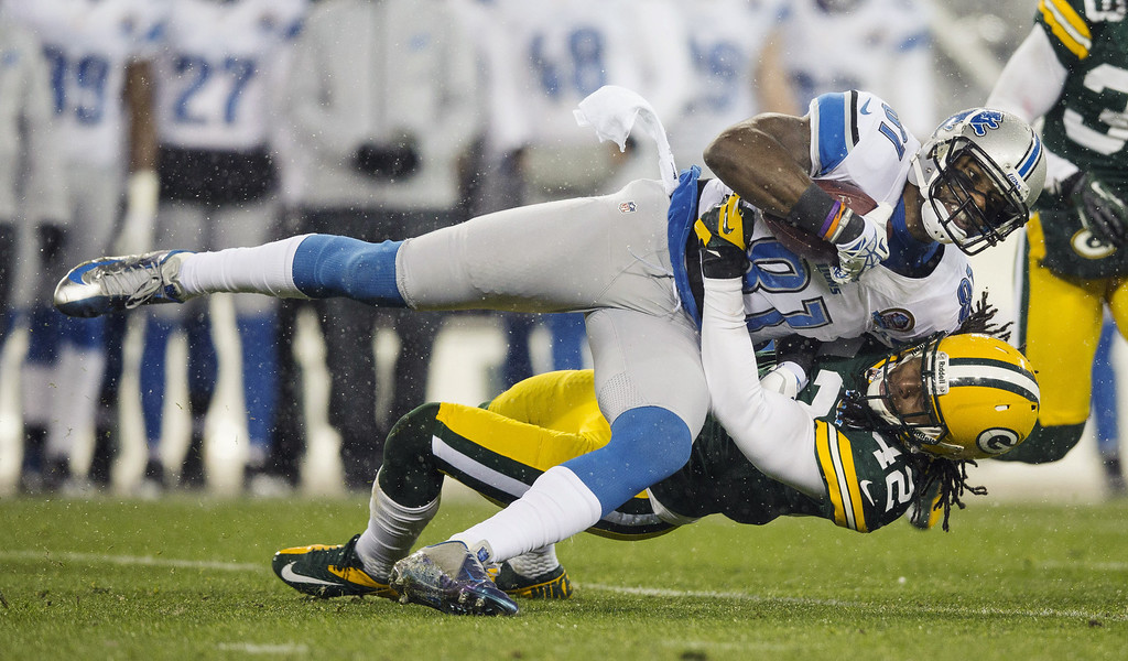 . GREEN BAY, WI - DECEMBER 9:  Calvin Johnson #81 of the Detroit Lions makes a catch and is tackled by Morgan Burnett #42 of the Green Bay Packers at Lambeau Field on December 9, 2012 in Green Bay, Wisconsin. (Photo by Tom Lynn /Getty Images)
