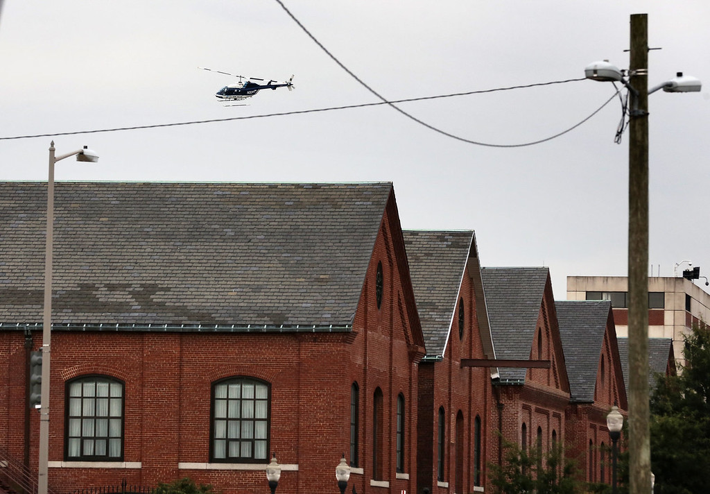 Description of . A police helicopter circles around above the Washington Navy Yard after a shooting rampage happened September 16, 2013 in Washington, DC. Police believe there to be as many as two shooters who killed several people and wounded others in an incident that put parts of the city on lockdown.  (Photo by Alex Wong/Getty Images)