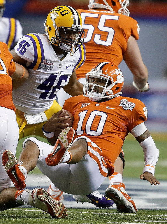 . Clemson quarterback Tajh Boyd (10) heads to the turf after a short run as LSU linebacker Kevin Minter (46) defends during the first half of the Chick-fil-A Bowl NCAA college football game, Monday, Dec. 31, 2012, in Atlanta. (AP Photo/David Goldman)