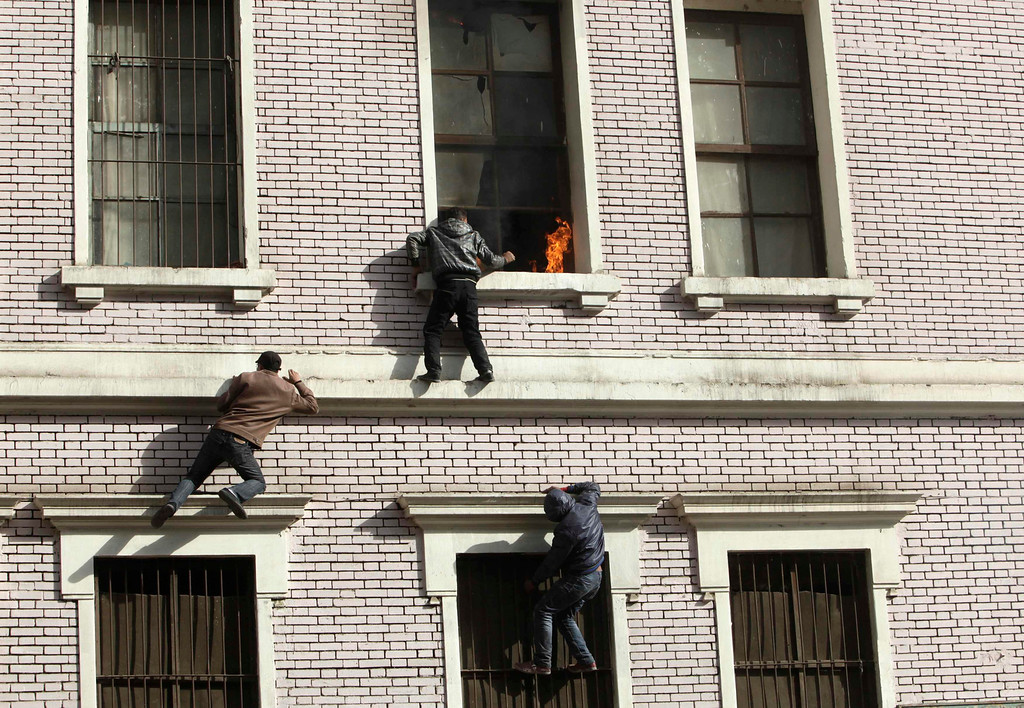 Description of . Protesters try to scale an apartment building to put out a fire that began when a tear gas canister was thrown into the building during clashes between police and protesters, near the Interior Ministry in Cairo, February 3, 2012. Egyptians incensed by the deaths of 74 people in soccer violence staged protests in central Cairo as the army-led government came under fire for failing to prevent the deadliest incident since the overthrow of Hosni Mubarak. REUTERS/Asmaa Waguih