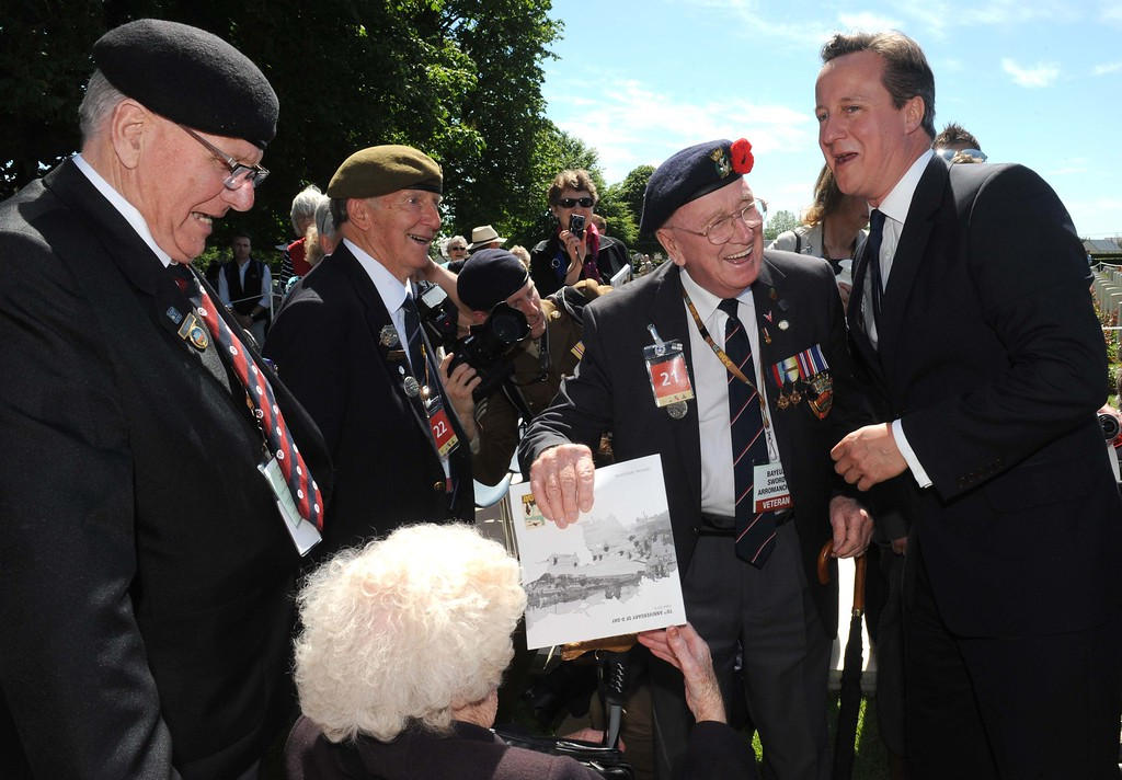 Description of . British Prime Minister David Cameron (R) speaks with a British veteran  during a bi-national France-UK D-Day commemoration ceremony at the British War Cemetery of Bayeux, on June 6, 2014, marking the 70th anniversary of the World War II Allied landings in Normandy. AFP PHOTO / POOL / THOMAS BREGARDIS/AFP/Getty Images