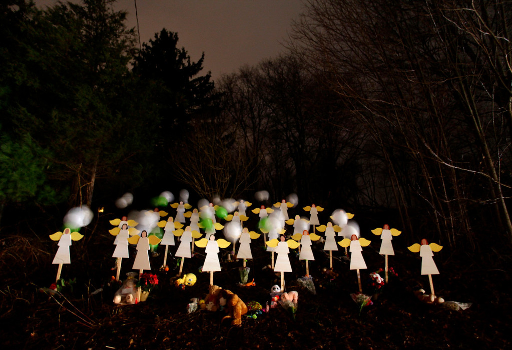 Description of . Twenty-seven wood painted angels are displayed outside of a home to honor the victims killed at Sandy Hook Elementary School in Newtown, Connecticut December 16, 2012. Twelve girls, eight boys and six adult women were killed in the shooting on Friday at Sandy Hook Elementary School in Newtown. REUTERS/Joshua Lott