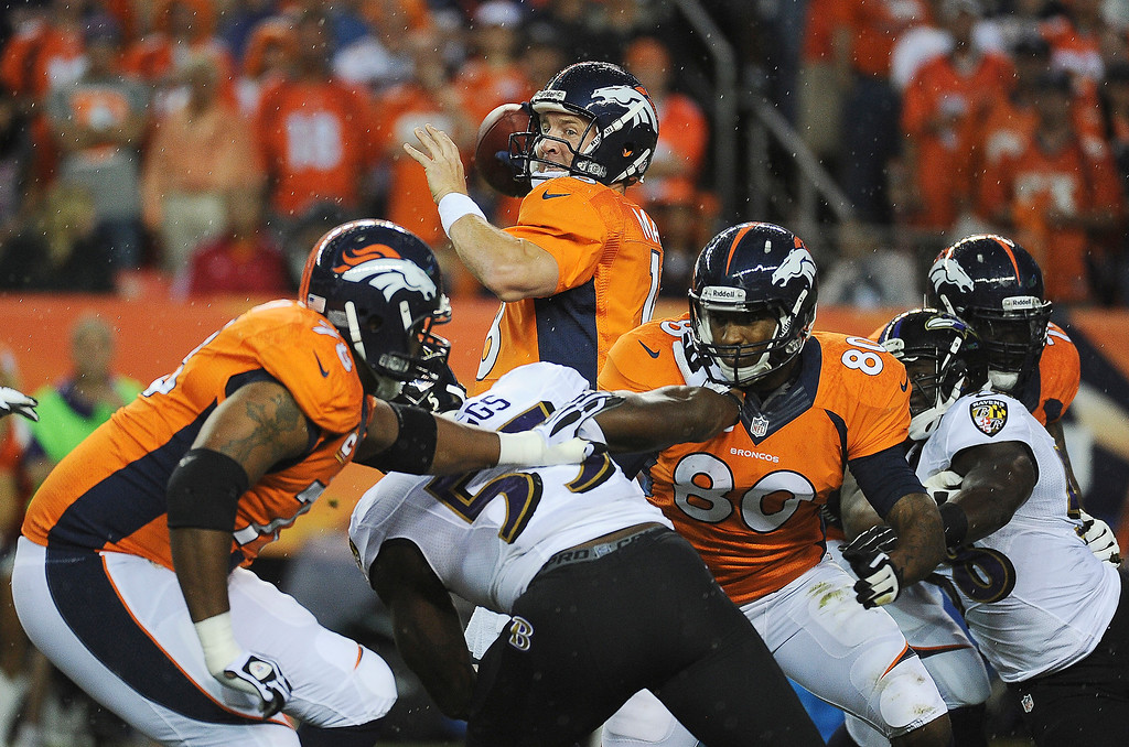 Description of . Denver Broncos quarterback Peyton Manning (18) drops back to pass in the first quarter.  (Photo by Tim Rasmussen/The Denver Post)