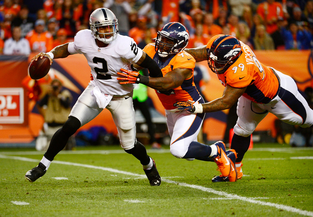 Description of . Denver Broncos defensive tackle Kevin Vickerson (99) and Denver Broncos defensive end Robert Ayers (91) chase Oakland Raiders quarterback Terrelle Pryor (2) out of the pocket in the first quarter. The Denver Broncos took on the Oakland Raiders at Sports Authority Field at Mile High in Denver on September 23, 2013. (Photo by Tim Rasmussen/The Denver Post)