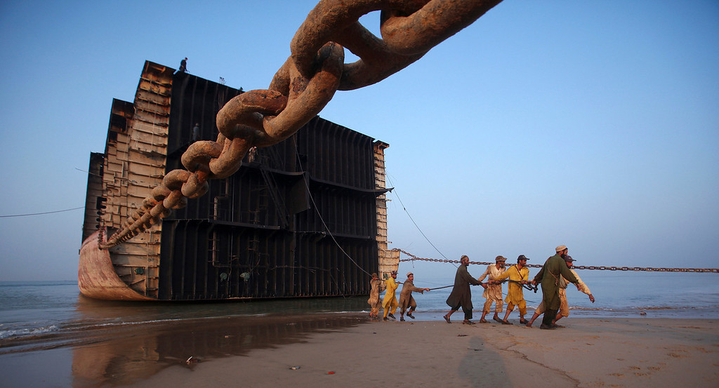 Description of . Laborers pull an iron rope before separating a portion of a ship into scrap metal at Gaddani ship breaking yard, about 60 km (37 miles) from Karachi November 25, 2011.  Pakistan is full of dangers, with tens of thousands of victims of suicide bombings, sectarian violence and ethnic bloodshed which make big headlines across the world. There is another less dramatic, but dark, side of the South Asian nation that rarely captures attention -- the large number of impoverished people forced to endure horrible conditions at work to survive. Fifteen thousand of them risk their lives every day, tearing down ships at Gaddani beach on the Arabian Sea coast, a 10 km-long death trap. They earn as little as $4 a day. Picture taken November 25, 2011. REUTERS/Akhtar Soomro
