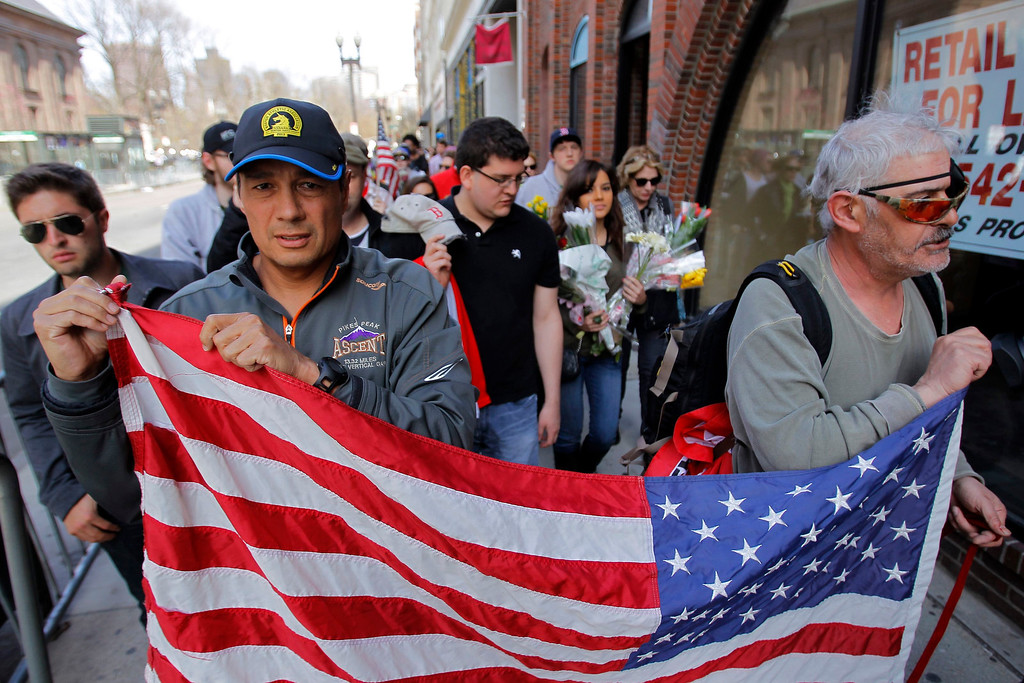 Description of . People move items from a vigil after the barricade they were hanging on was taken down and a portion of Boylston Street reopened a day after two explosions near the finish line of the Boston Marathon in Boston, Massachusetts April 16, 2013. A pressure cooker stuffed with gunpowder and shrapnel caused at least one of the blasts at the Boston Marathon that killed three people and injured 176 others in the worst attack on U.S. soil since September 11, 2001, law enforcement sources said on Tuesday.  REUTERS/Jessica Rinaldi