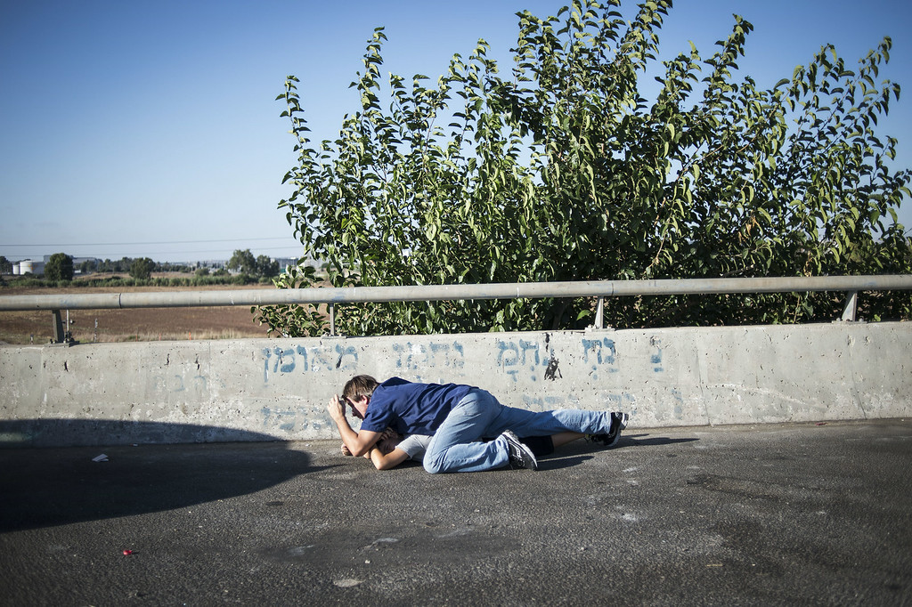 Description of . Israelis seen taking cover on a highway as a siren sounds on July 17, 2014 in Tel-aviv, Israel. As the Israeli operation 'Protective Edge' enters it's tenth day, the body count in Gaza has reach over 200 people. One Israeli has been killed in a Mortar attack.  (Photo by Ilia Yefimovich/Getty Images)