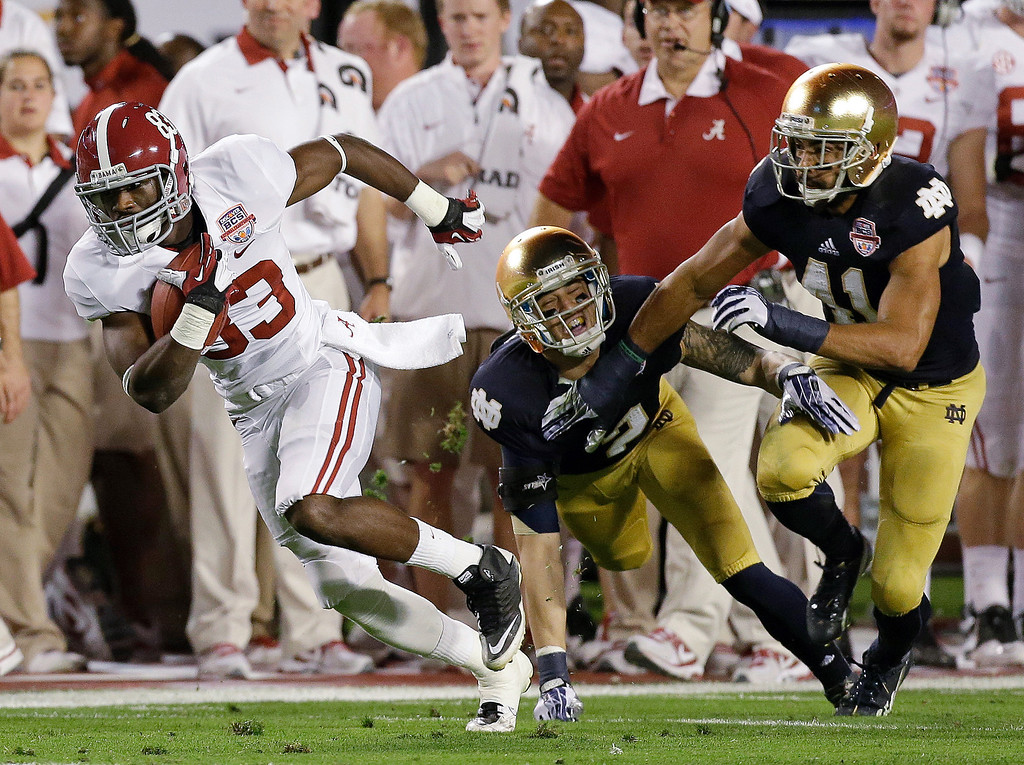 Description of . Alabama's Kevin Norwood (83)catches a pass in front of Notre Dame's Bennett Jackson (2) and Matthias Farley (41) during the first half of the BCS National Championship college football game Monday, Jan. 7, 2013, in Miami. (AP Photo/Chris O'Meara)
