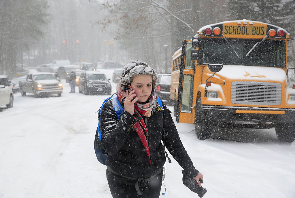 Description of . Katharine Newton, a student at the University of North Carolina at Chapel Hill, calls her parents while walking more than two miles from campus to her parents\' home during a snow storm in Chapel Hill, NC, on Wednesday, Feb. 12, 2014.  Roads were blocked and Newton was unable to drive.  (AP Photo/Ted Richardson)