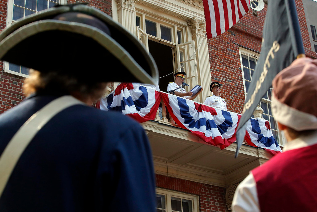 Description of . Re-enactors in period attire listen as a member of the Ancient and Honorable Artillery Company reads the United States Declaration of Independence from the balcony of the Old State House, part of Fourth of July Independence Day celebrations, in Boston, Massachusetts July 4, 2013. People across the United States gathered on Thursday for parades, picnics and fireworks at Independence Day celebrations, held under unprecedented security following the Boston Marathon bombings. Spectators waving U.S. flags and wearing red, white and blue headed for public gatherings in Boston, New York, Washington, Atlanta and other cities under the close watch of police armed with hand-held chemical detectors, radiation scanners and camera surveillance, precautions sparked by the deadly April 15 bombings. REUTERS/Brian Snyder