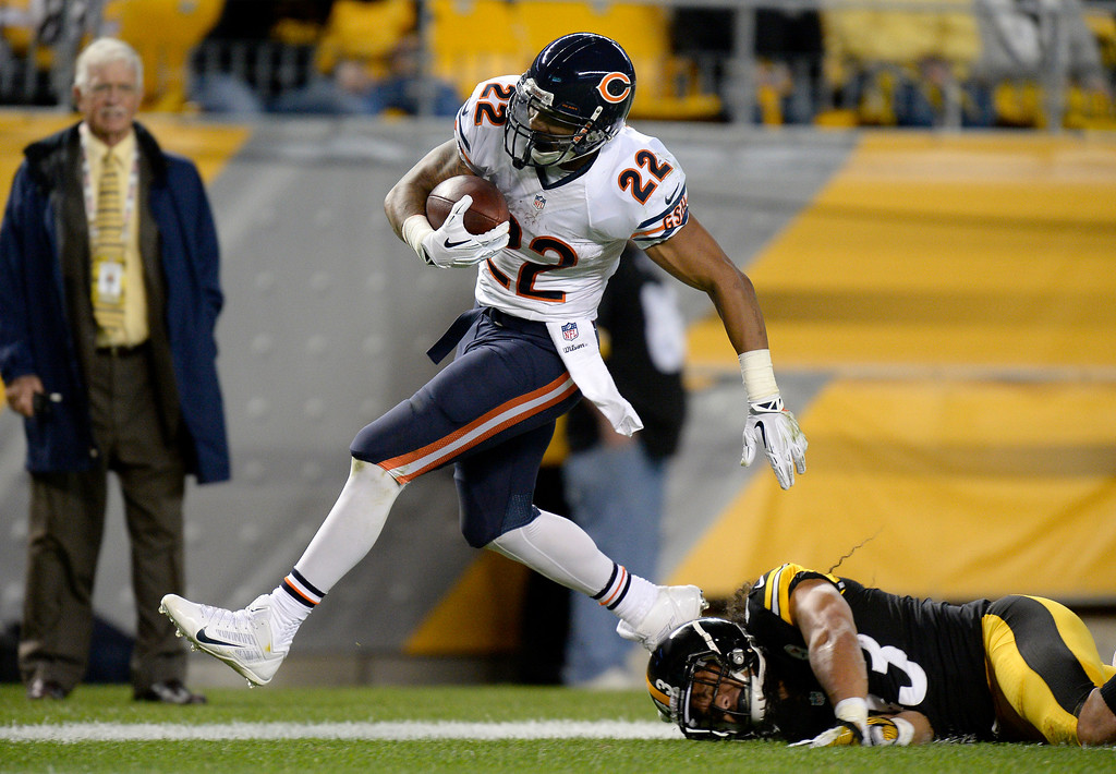 Description of . Chicago Bears running back Matt Forte (22), steps out of bounds after getting hit by Pittsburgh Steelers strong safety Troy Polamalu (43) on a long run in the first quarter of an NFL football game on Sunday, Sept. 22, 2013, in Pittsburgh. (AP Photo/Don Wright)