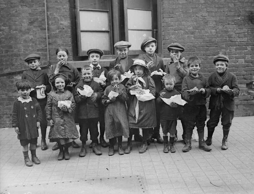 Description of . 3rd March 1917:  Children eating a penny's worth of Plum Duff from soup kitchens in Bermondsey, south London.  (Photo by Topical Press Agency/Getty Images)