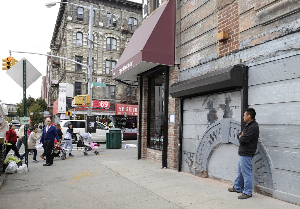 Description of . Feliciano Perez guards the work by British graffiti artist Banksy on Saturday, Oct. 19, 2013, in the Brooklyn borough of New York. The building owner has hired security guards and installed a metal gate to protect a work by Banksy. Cara Tabachnick, whose family owns the building, said the goal is to preserve the artwork