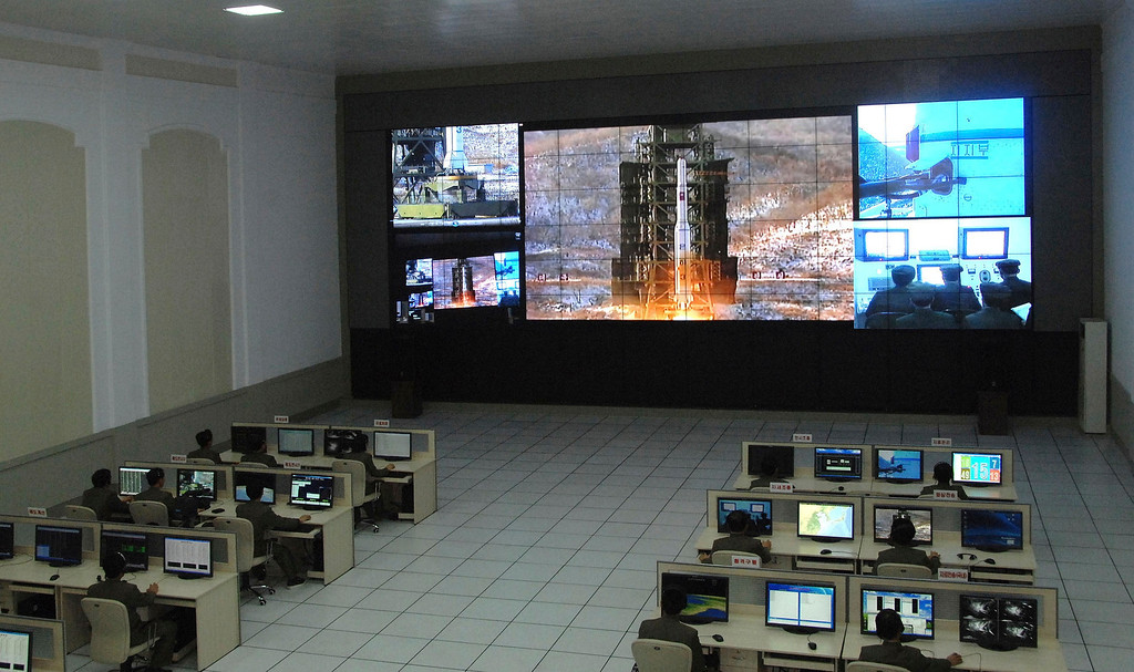 . North Korean scientists work as a screen shows the Unha-3 (Milky Way 3) rocket being launched from a launch pad at the West Sea Satellite Launch Site, at the satellite control centre in Cholsan county, North Pyongan province in this picture released by the North\'s official KCNA news agency in Pyongyang December 12, 2012. KCNA said the picture was taken December 12, 2012.    REUTERS/KCNA