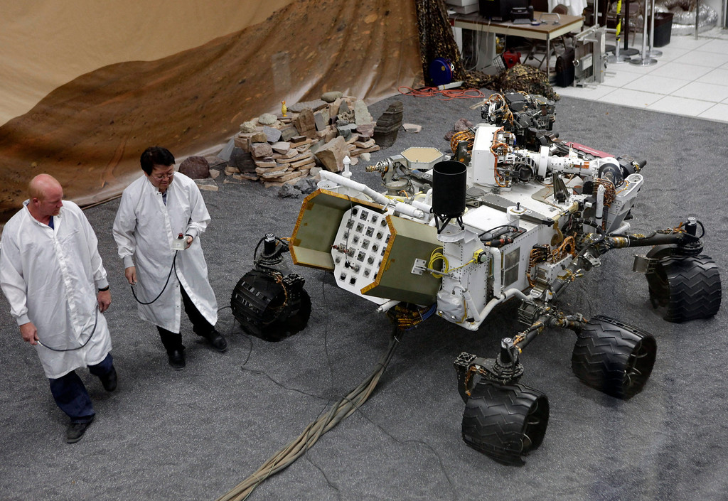 Description of . FILE - In this Thursday, Aug. 2, 2012 file photo, engineers work on a model of the Mars rover Curiosity at the Spacecraft Assembly Facility at NASA's Jet Propulsion Laboratory in Pasadena, Calif. (AP Photo/Damian Dovarganes)